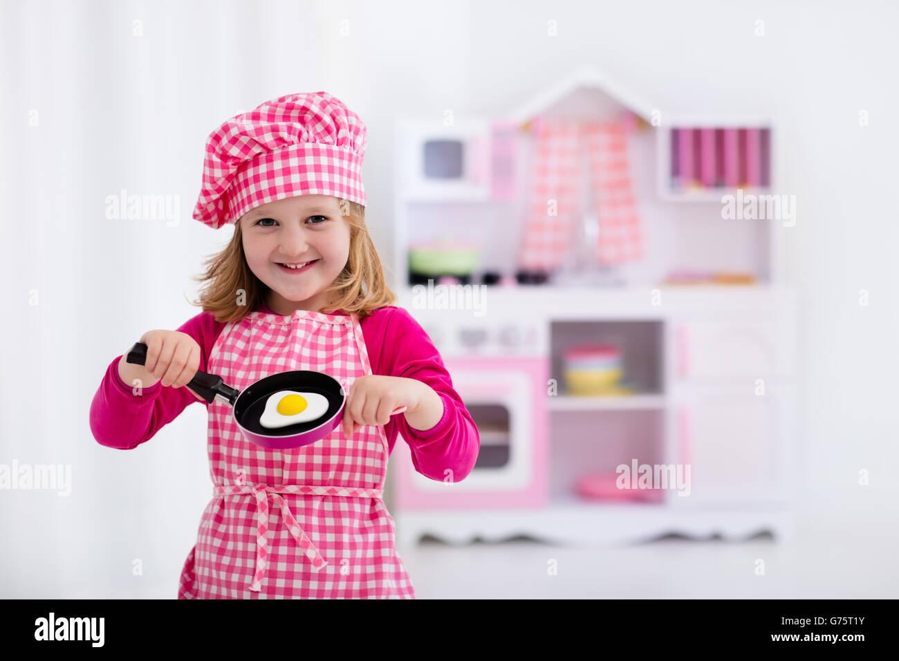 Kleines Mädchen in Koch Hut und Schürze Spiegeleier in Spielzeug ...