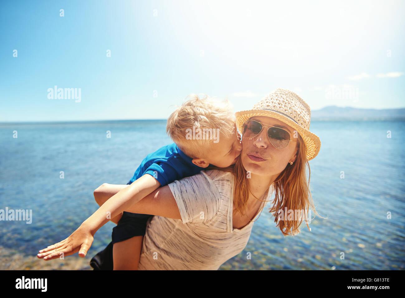 Liebevolle kleine Junge Reiten Huckepack gelehnt von hinten nach vorne und küsste seine Mutter in ein bewegender Stockbild