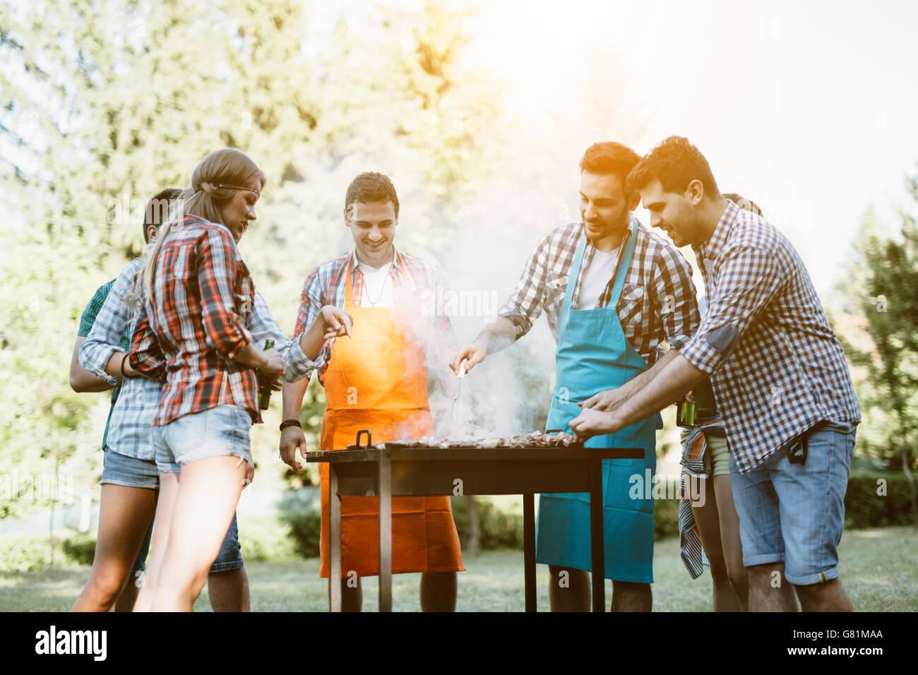 Junge Menschen, die genießen, Grillen Stockbild