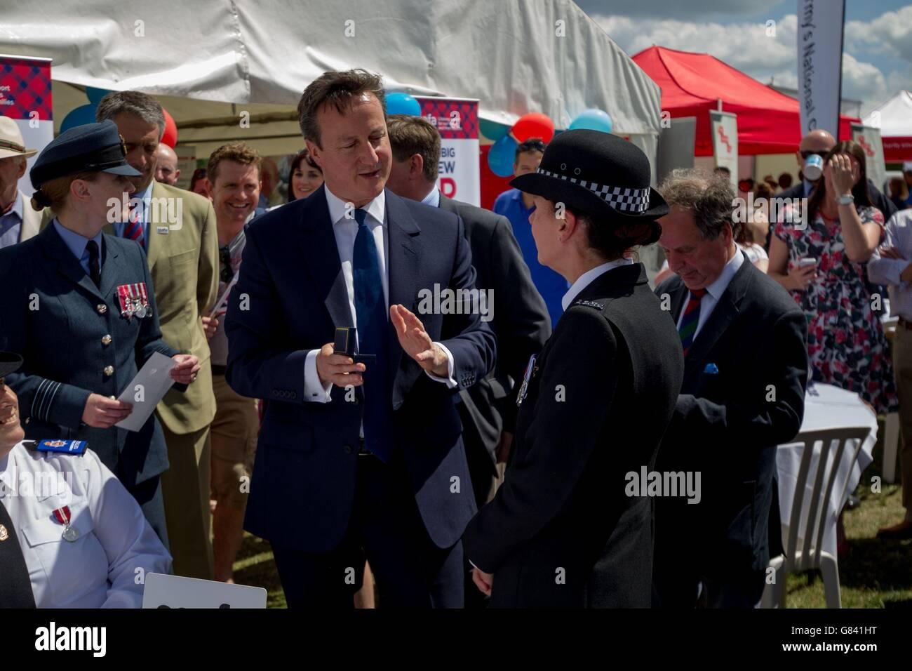 Premierminister David Cameron betrachtet Exponate im Stoke Park am Tag der Streitkräfte in Guildford. Stockfoto