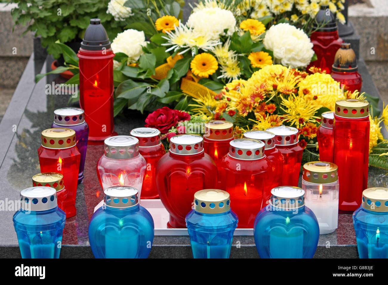 Blumen und Kerzen, die auf dem Grab, Laterne leuchtet Stockbild