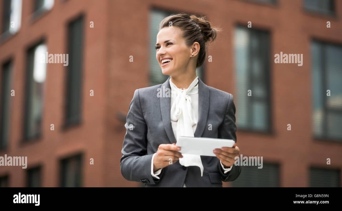 Das neue Geschäft. Moderne Business-Frau mit Tablet-PC gegen Bürogebäude beiseite suchen Stockfoto