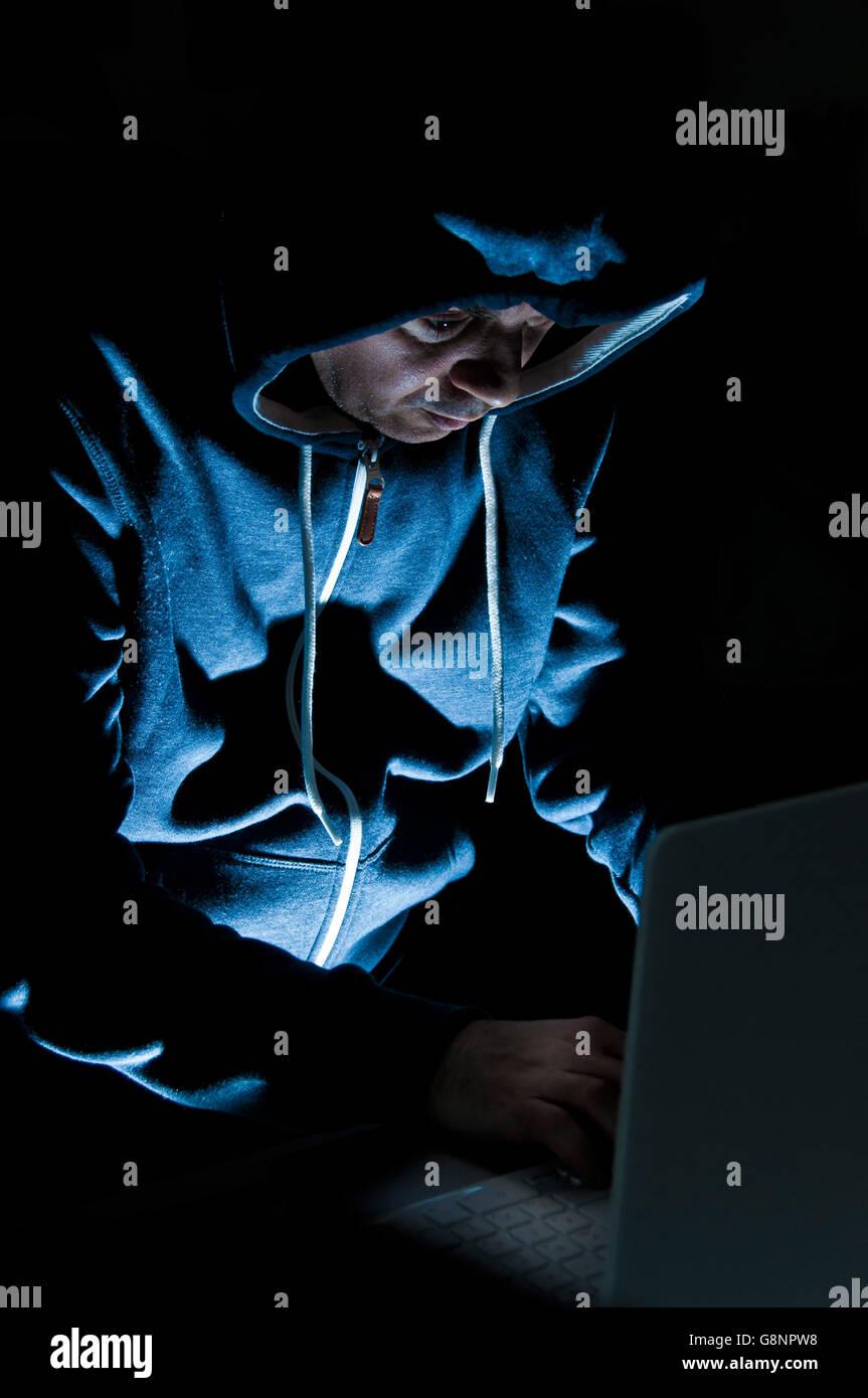Hacker in Aktion im Dunkeln Stockbild