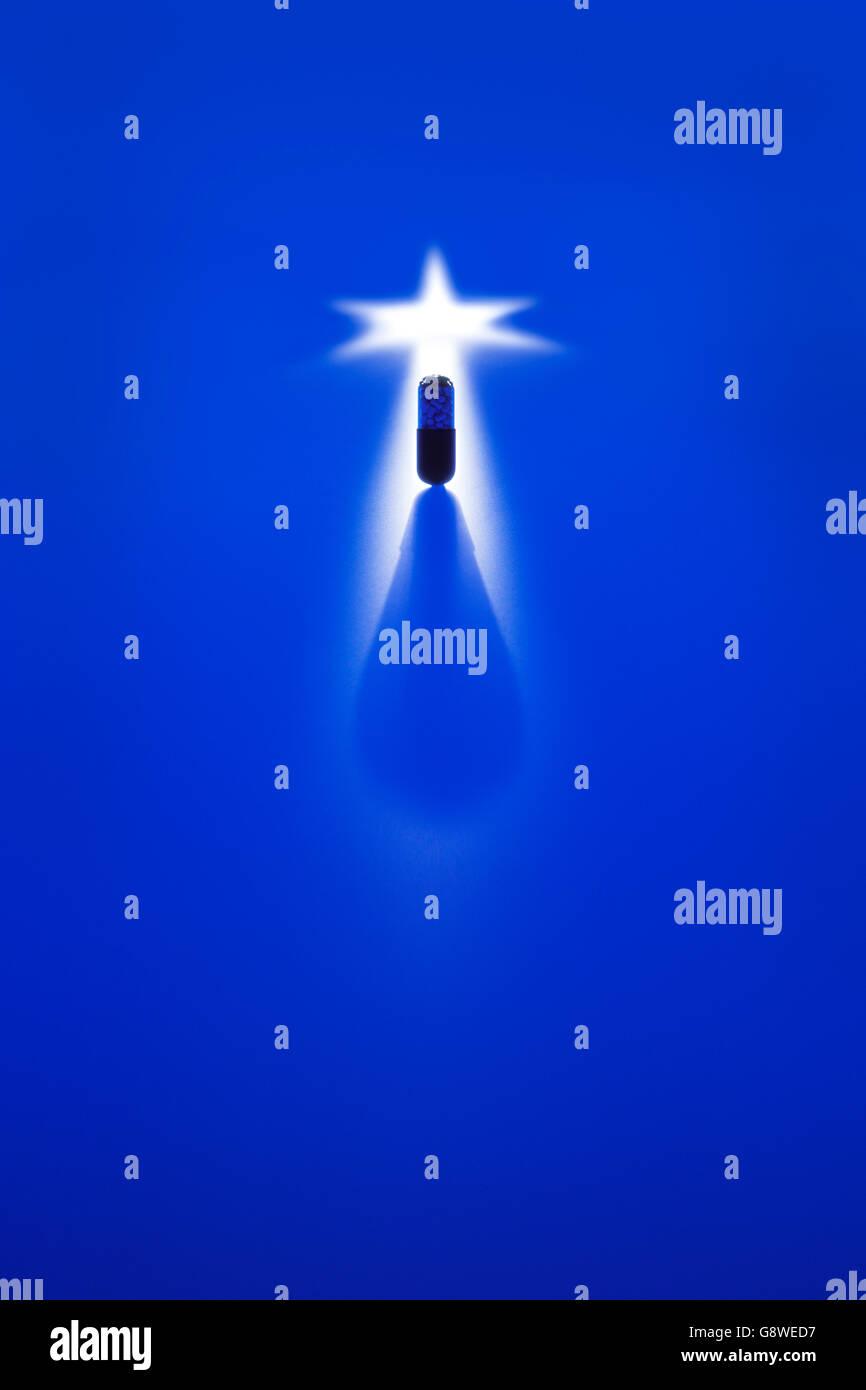 Dramatische Schuß von pharmazeutischen Kapsel vor blauem Hintergrund in Semi Silhouette Stockbild