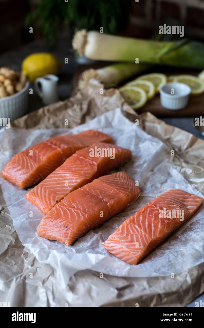 Vier Scheiben von frischem Lachs, Lauch, Zitronenscheiben werden aus der Vorderansicht fotografiert. Stockbild