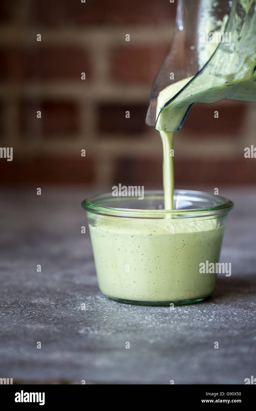 Eine Person ist grün Cashew-Sauce in ein klares Glas gießen. Stockbild
