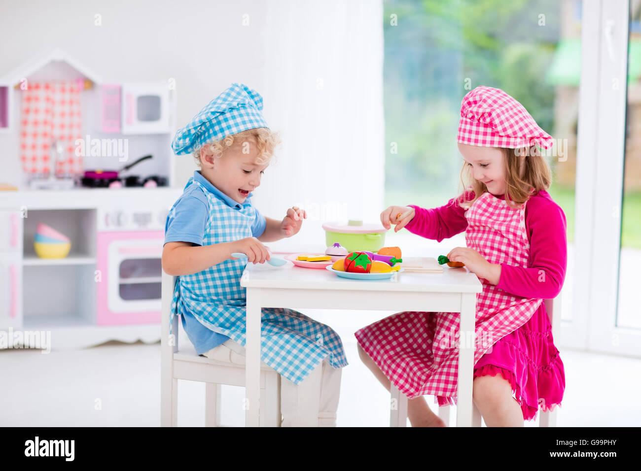 Kleine Mädchen und jungen in Koch Hut und Schürze in Spielzeug ...