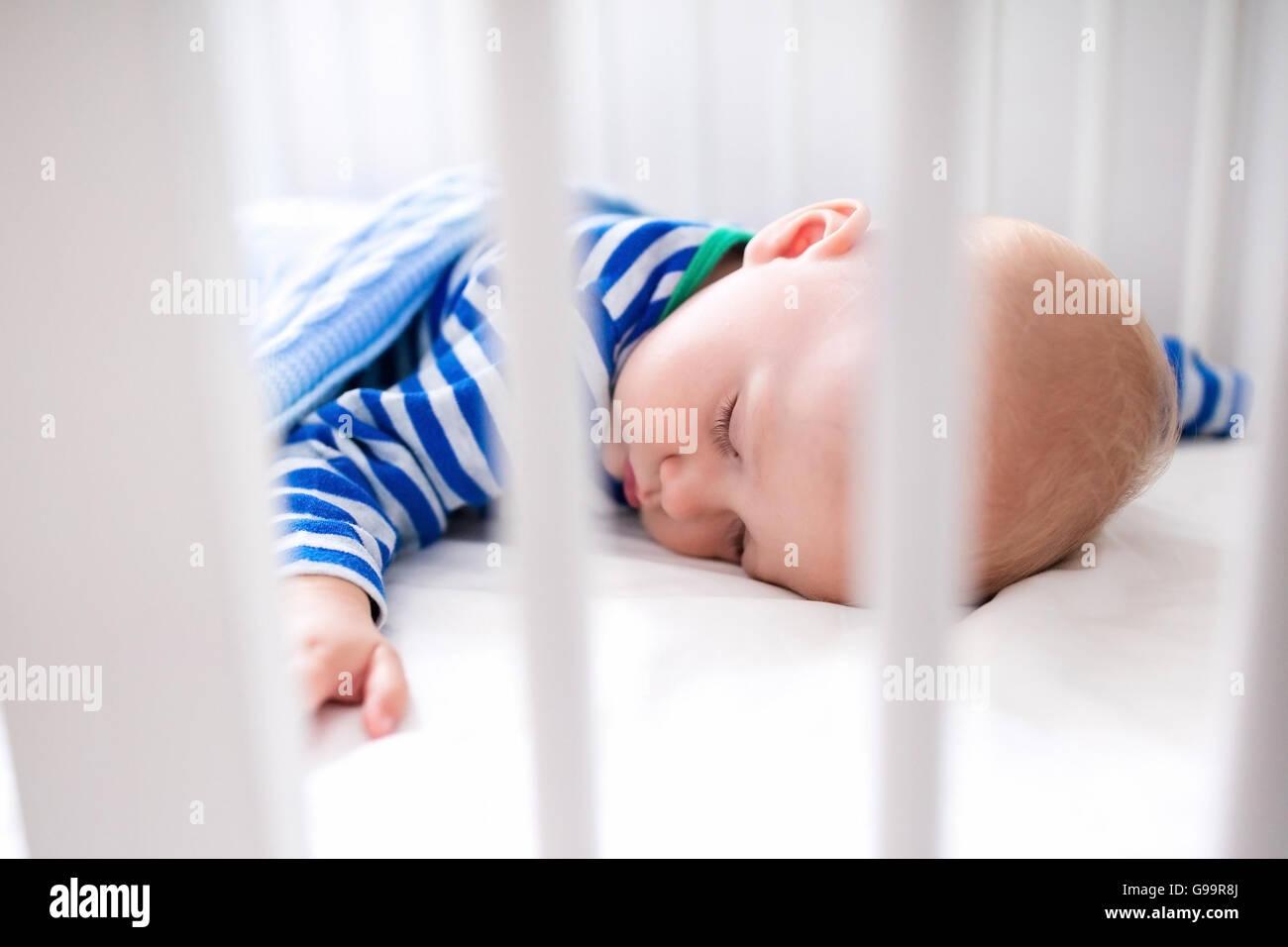 Schlafendes baby und sein spielzeug in weißen krippe. kindergarten