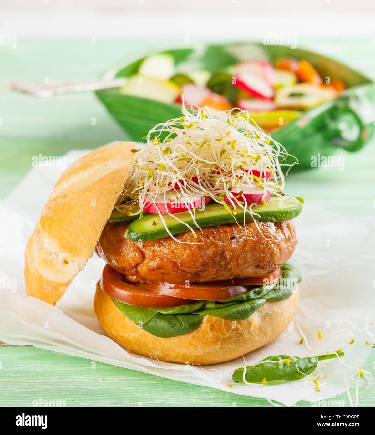 Ein köstliches Gourmet-Hamburger mit frischem Gemüse: Tomaten, Spinat, Gurken, Radieschen und Sprossen Stockbild