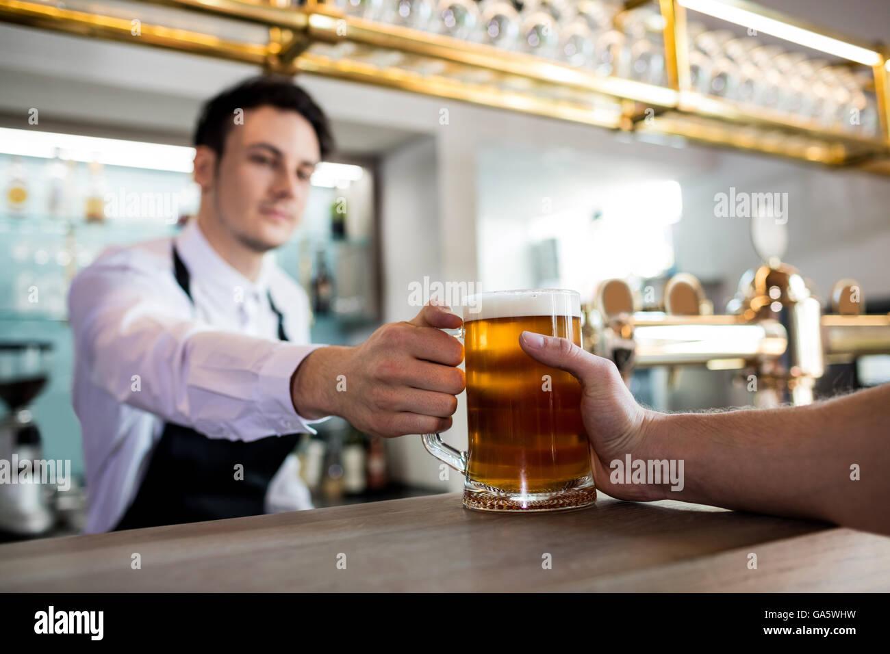 Barkeeper servieren Bier an Kunden Stockbild
