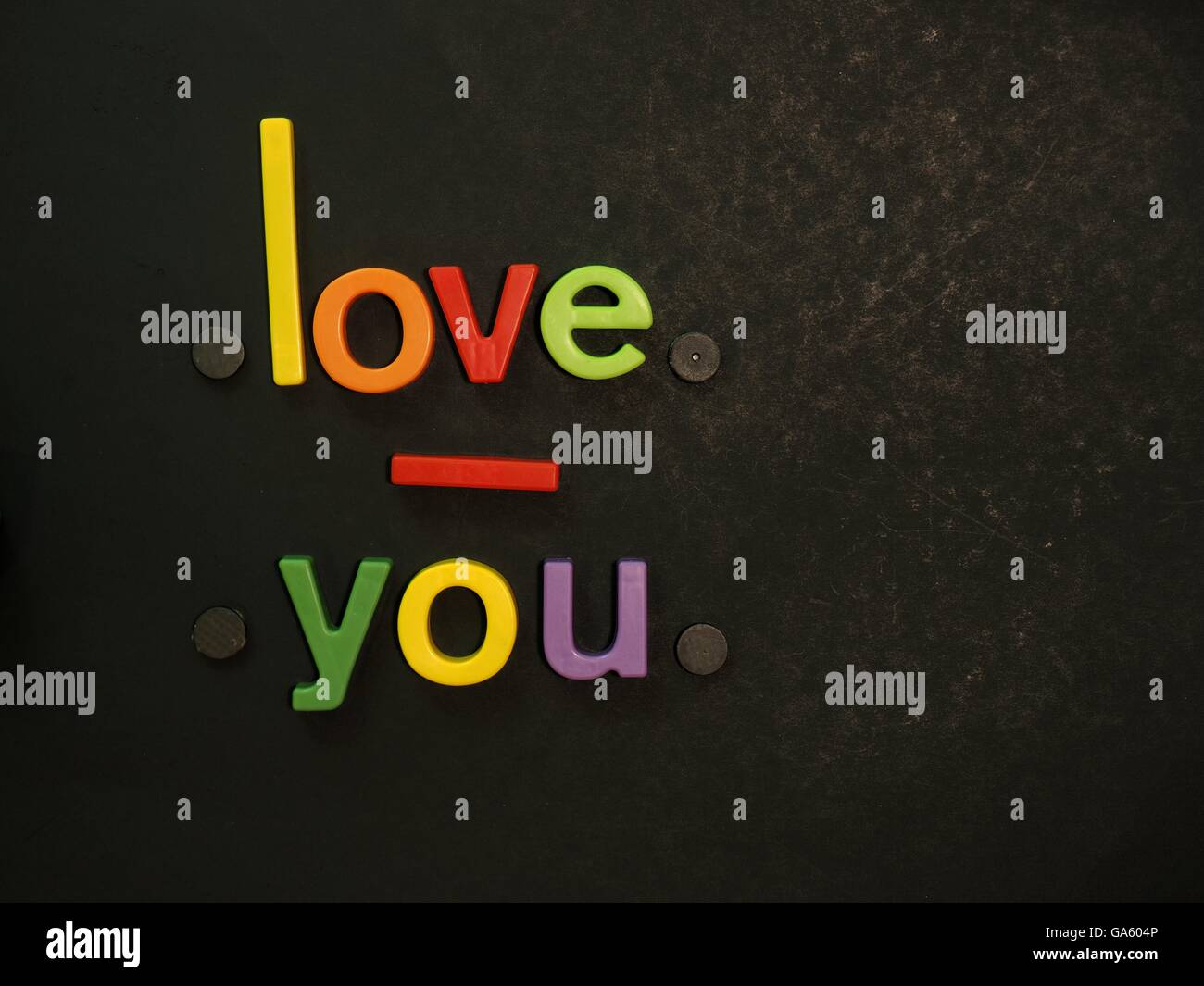Liebe dich! Inspirierende Botschaft in lebhaften bunten Magneten Buchstaben auf schwarzem Hintergrund Stockbild
