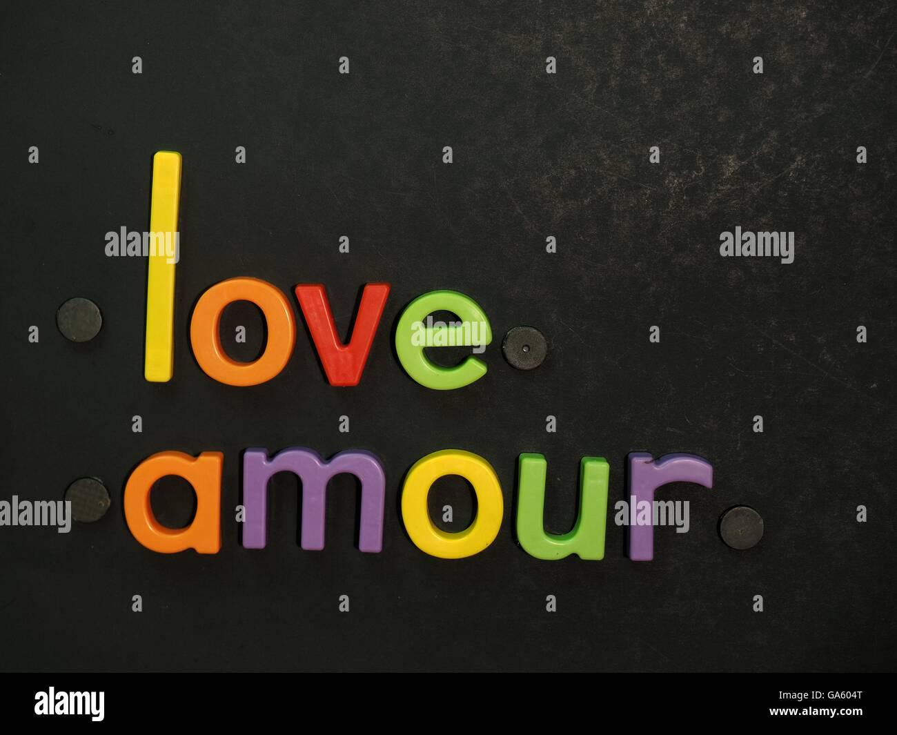 Liebe, Amour! Inspirierende Botschaft in lebhaften bunten Magneten Buchstaben auf schwarzem Hintergrund Stockbild