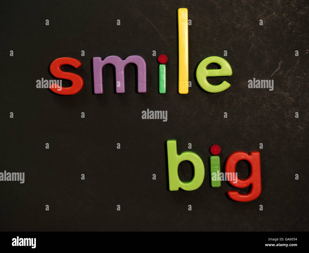 Lächeln! Inspirierende Botschaft in lebhaften bunten Magnet-Buchstaben Stockbild