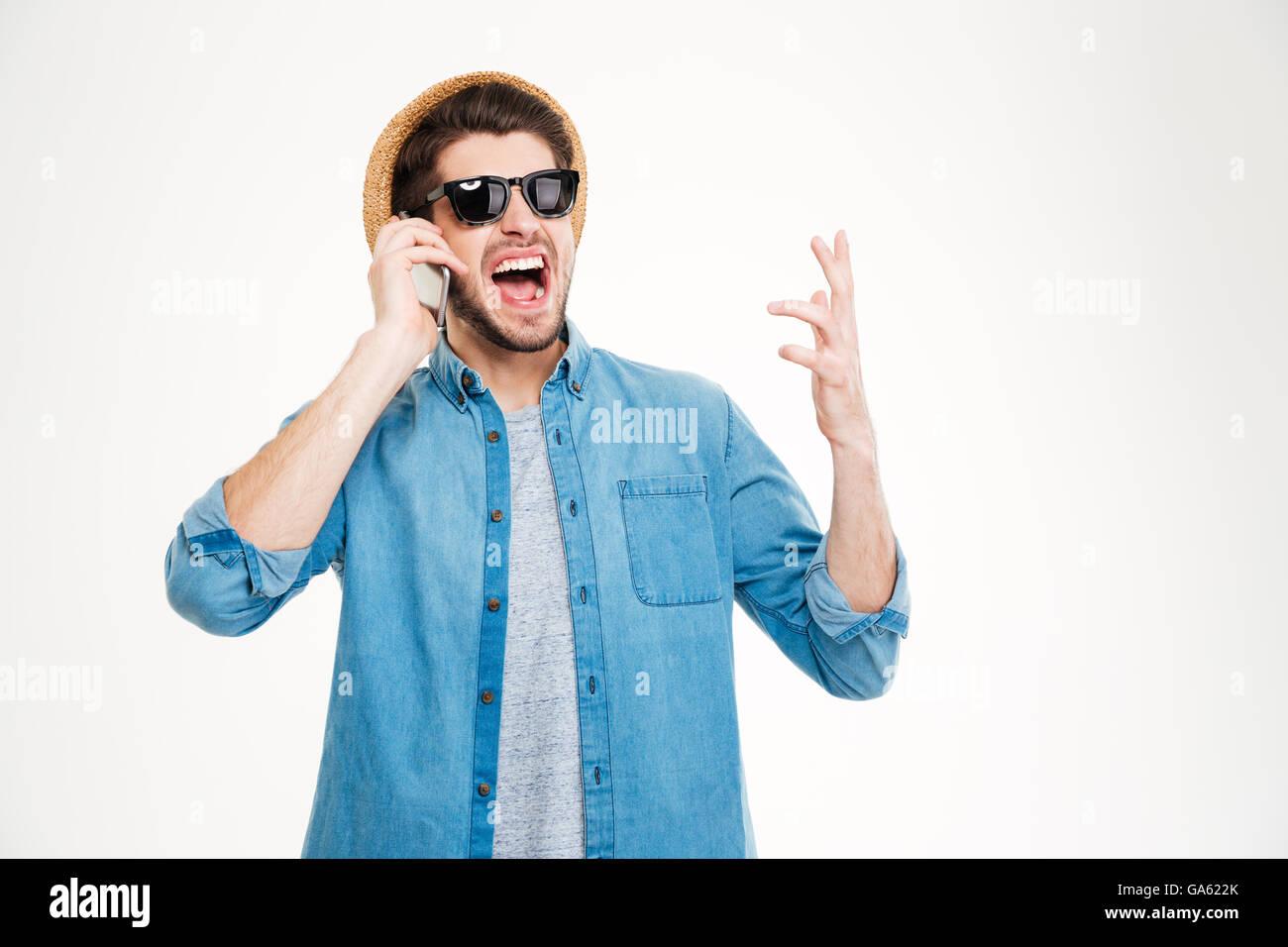 5f778e3f4c87cc Glücklich aufgeregt junger Mann in Hut und eine Sonnenbrille reden über  Handy auf weißem Hintergrund