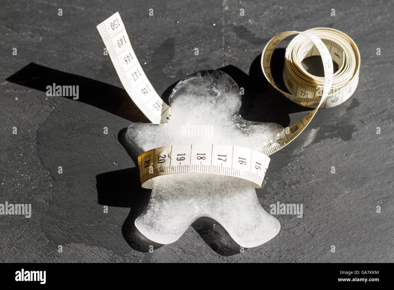 Verlor Gewicht und schlanke abstraktes Konzept mit Eis Körper Schmelzen und messen Stockbild