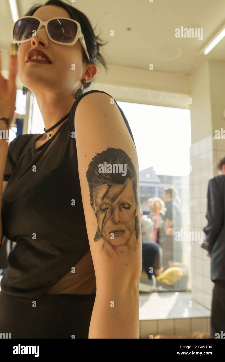 Junge Frau Mit Tattoo Von David Bowie Auf Dem Oberarm Tragen Große