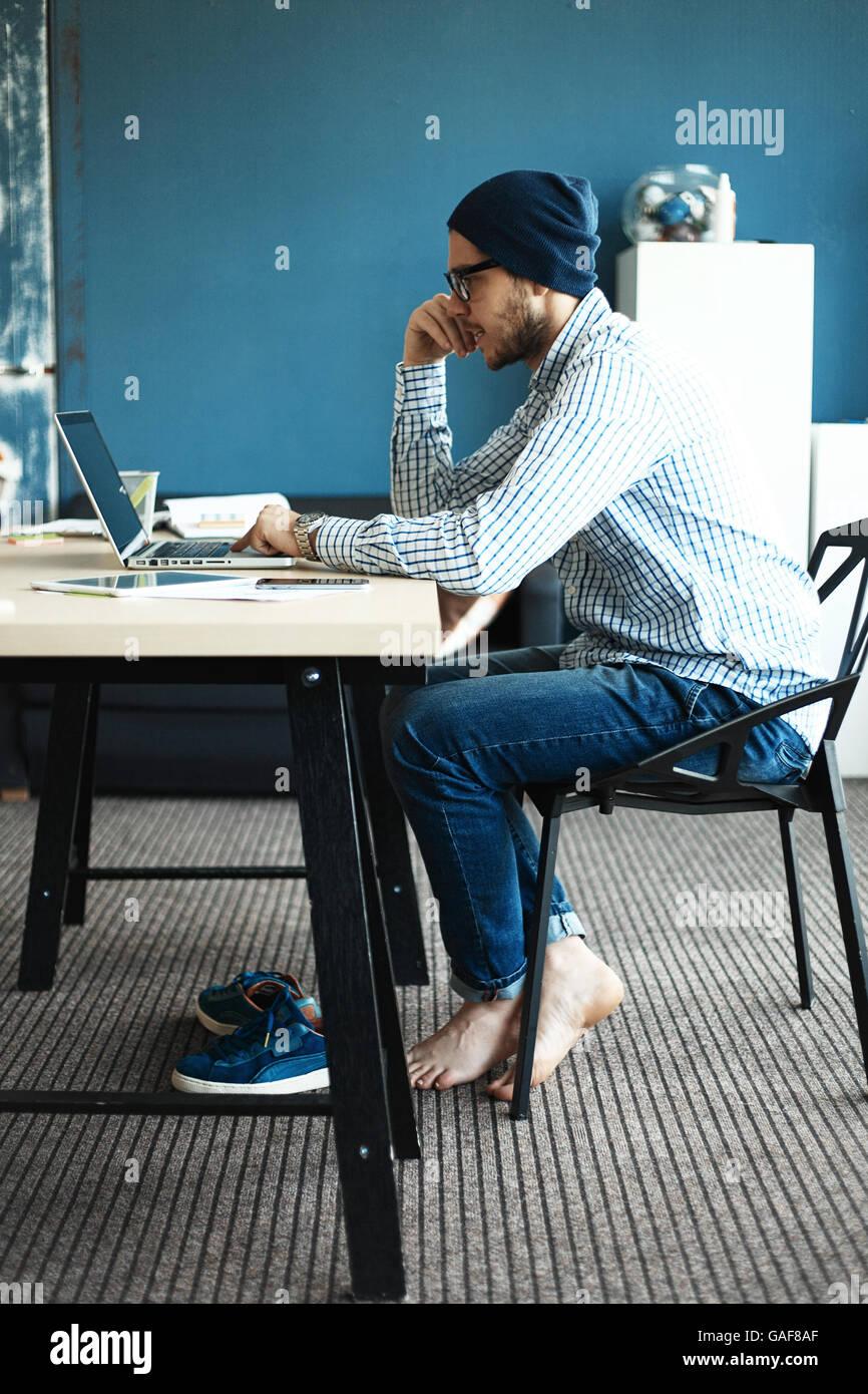 Hübscher Mann aus seinem Büro zu Hause arbeiten. Business-Pläne auf Laptop zu analysieren. Der Hintergrund jedoch Stockfoto