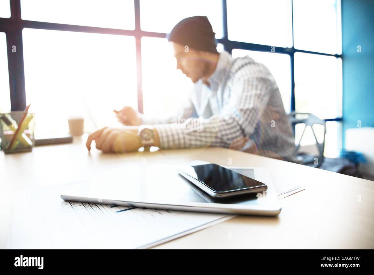 Büroarbeitsplatz mit Laptop auf Holz Tisch gegen Windows. Stockfoto