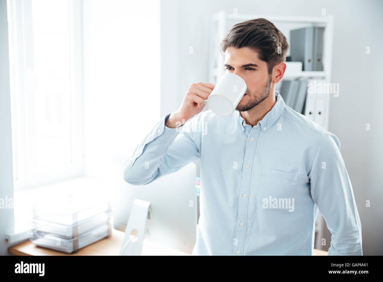 Hübscher junger Mann stehen und trinken Kaffee im Büro Stockbild