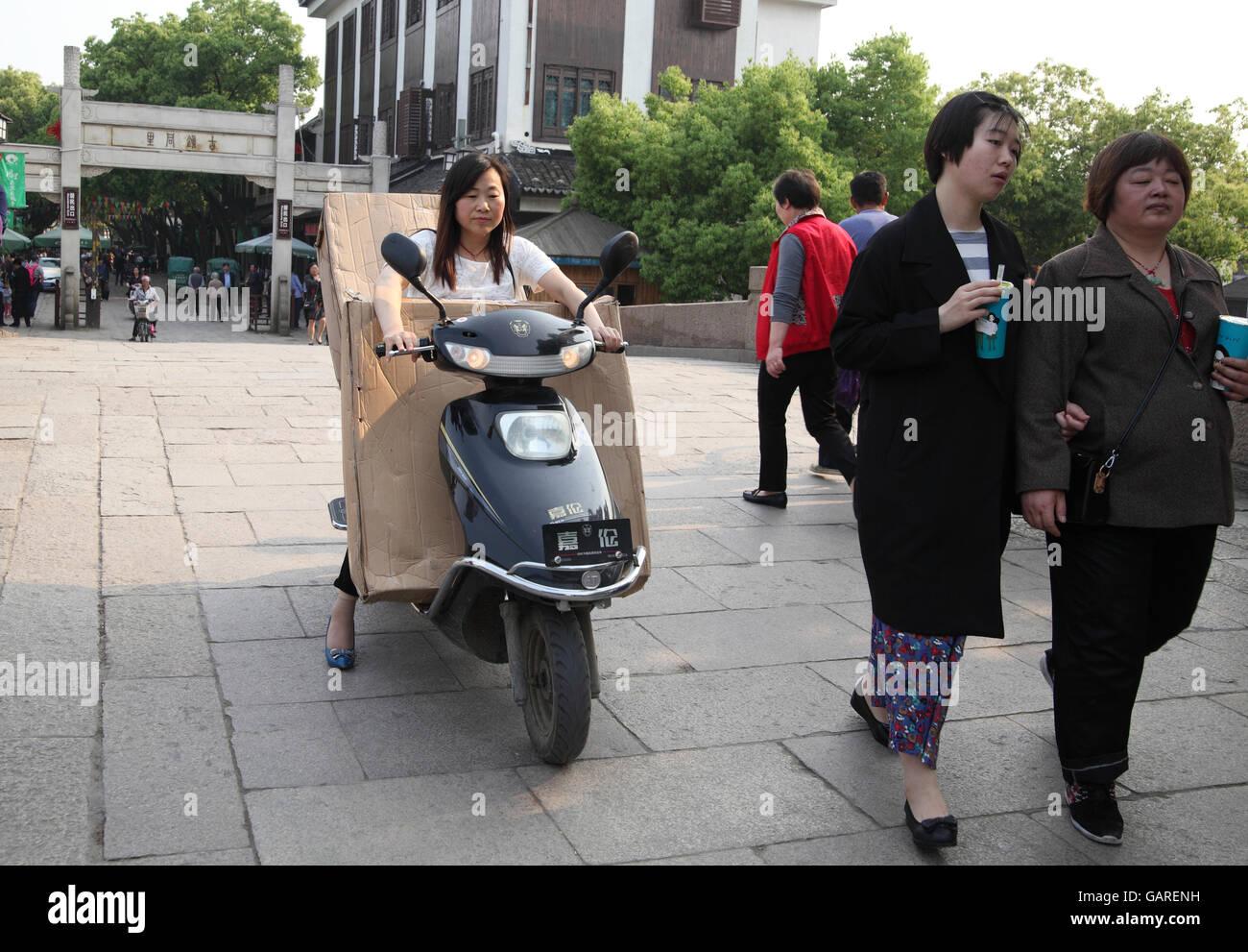 Eine Chinesin reitet ein Roller zu transportieren, die riesige Pakete, die sie, vor ihr und in den Rücken, Stockbild