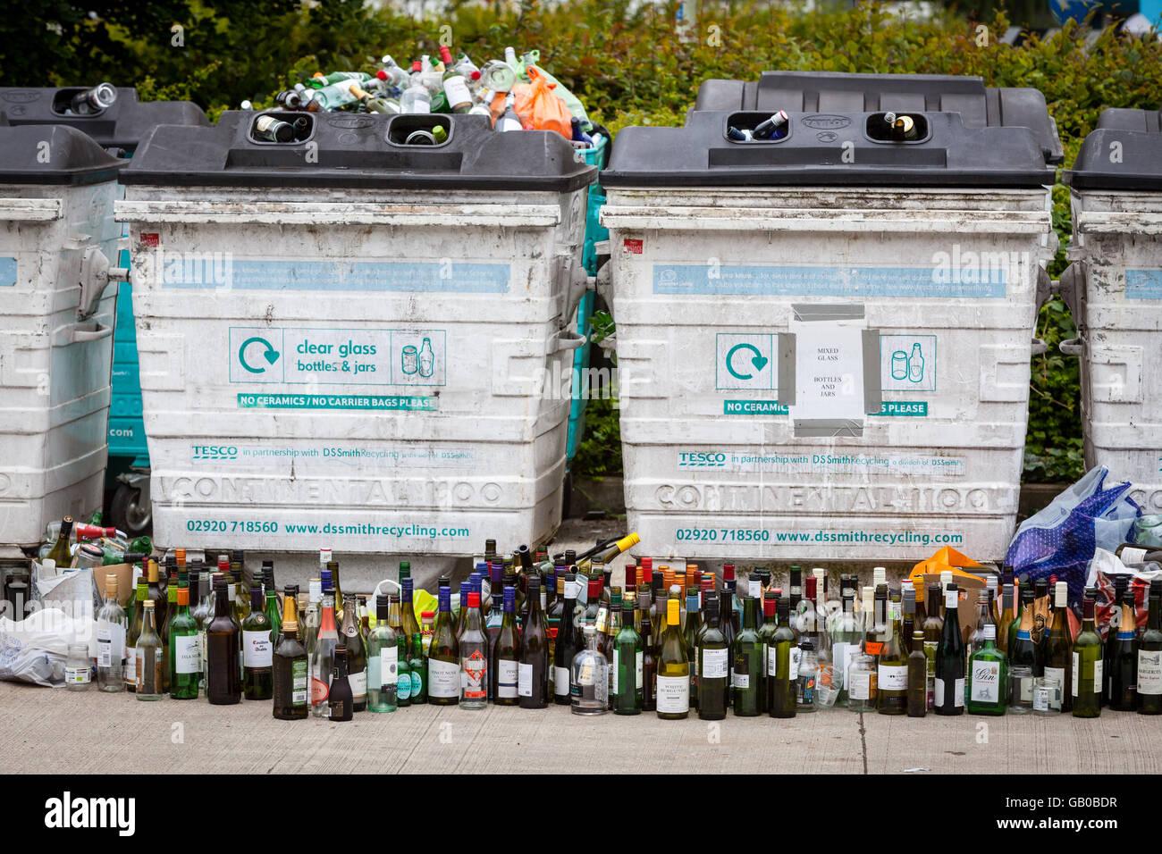 Recycling Glas Altglascontainer in Winchester, UK überlaufen mit Reihen von Weinflaschen aufgereiht vor Stockbild