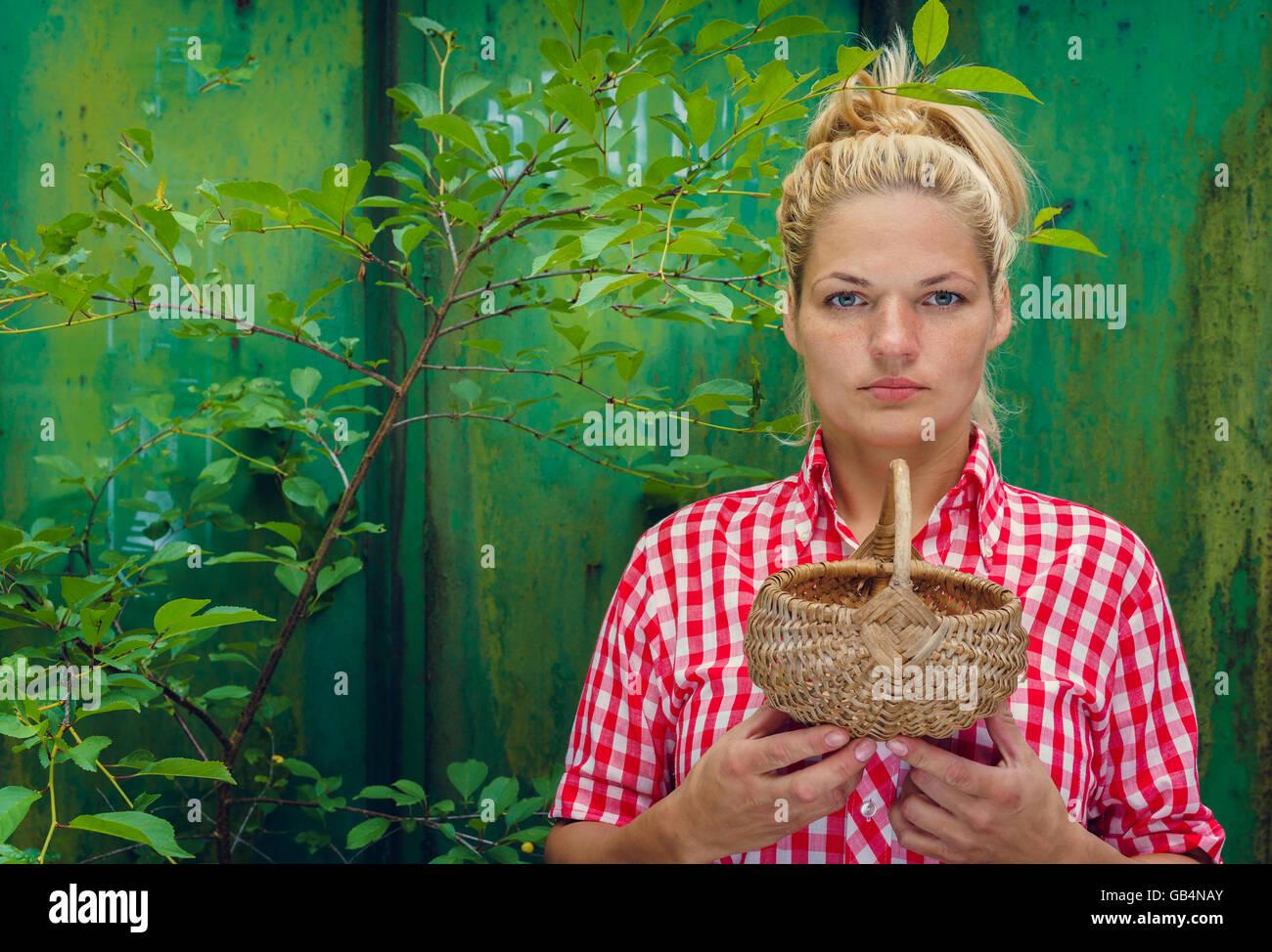 b2d3ee7f7c2055 Blonde Mädchen auf einem grünen Hintergrund hält einen Korb. Rockabilly-Style.  Platz für
