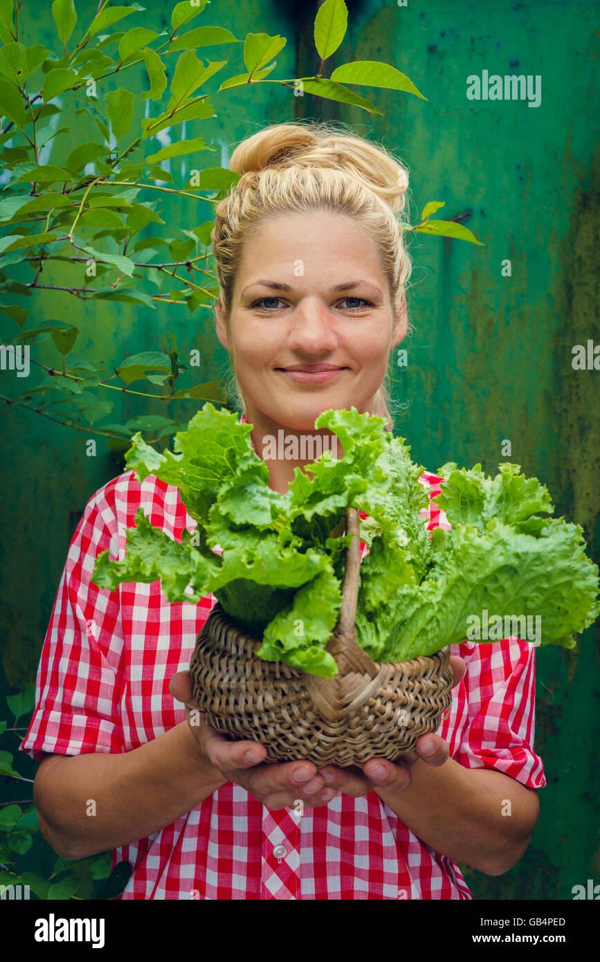 b8b59bcb79532c Blonde Mädchen auf einem grünen Hintergrund hält Korb mit Salat. Rockabilly-Style.  Platz