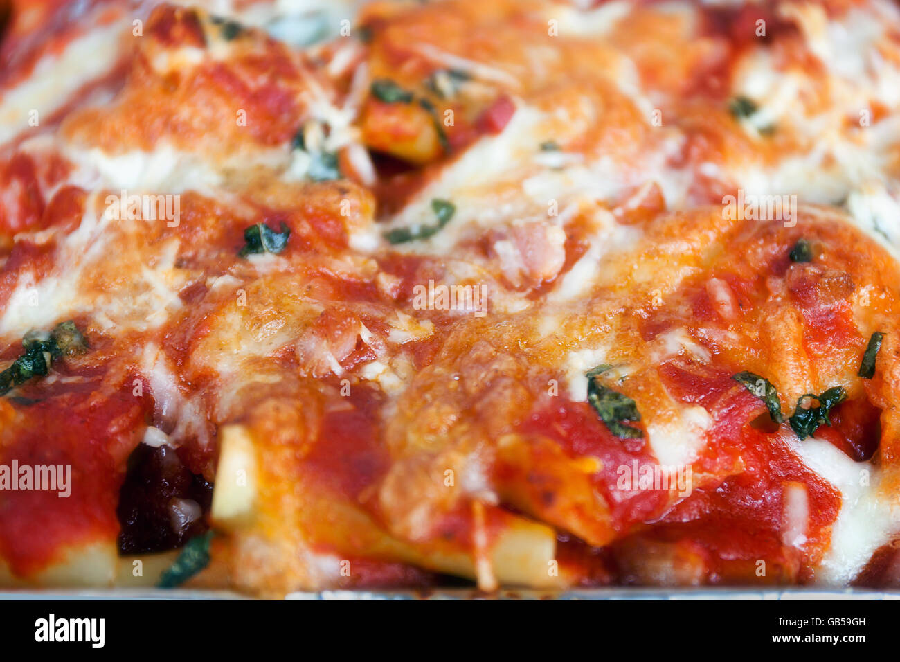 Überbacken mit Tomatensauce, Mozzarella, Speck und Basilikum. Italienische kulinarische Spezialitäten. Stockbild