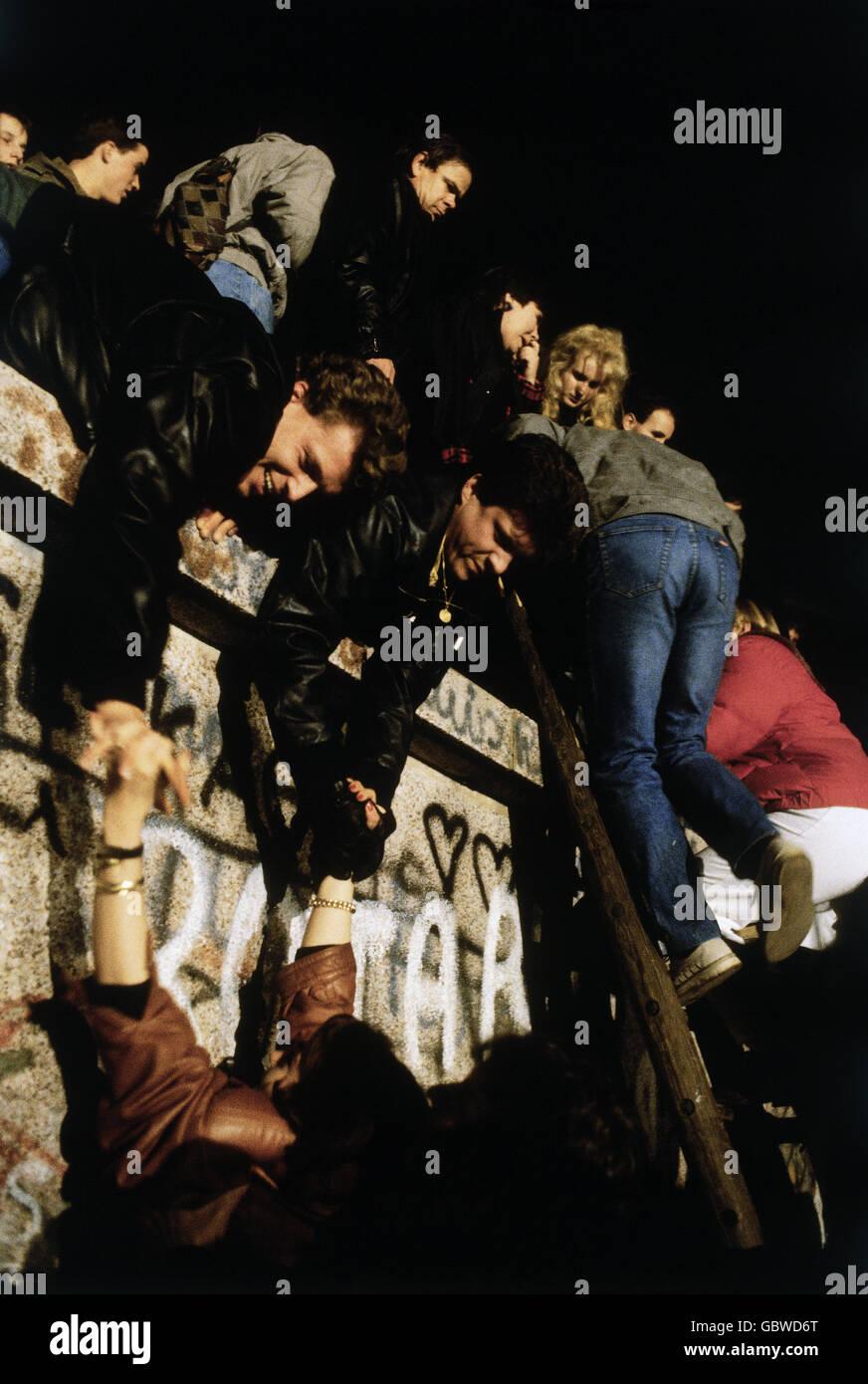 Deutschland, Wiedervereinigung, Fall der Berliner Mauer, Menschen klettern die Mauer, Berlin, 9.11.1989, DDR, BRD, Stockbild