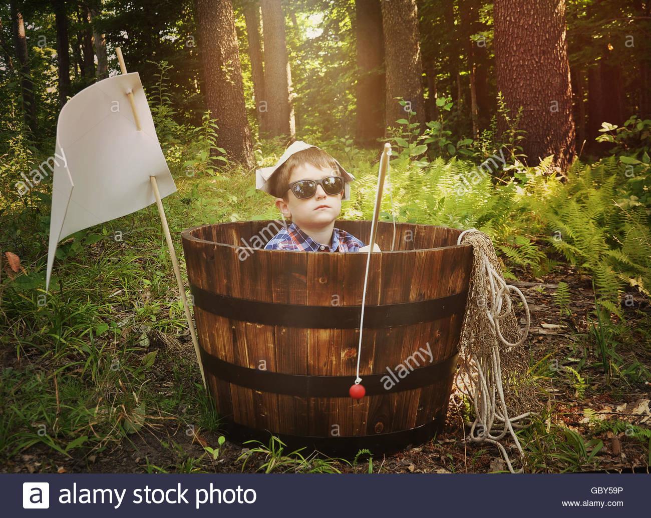 Ein kleiner Junge ist entspannend in einem Holzboot Fass mit Fischen Pol Spielzeug im Wald für eine Phantasie, Stockbild