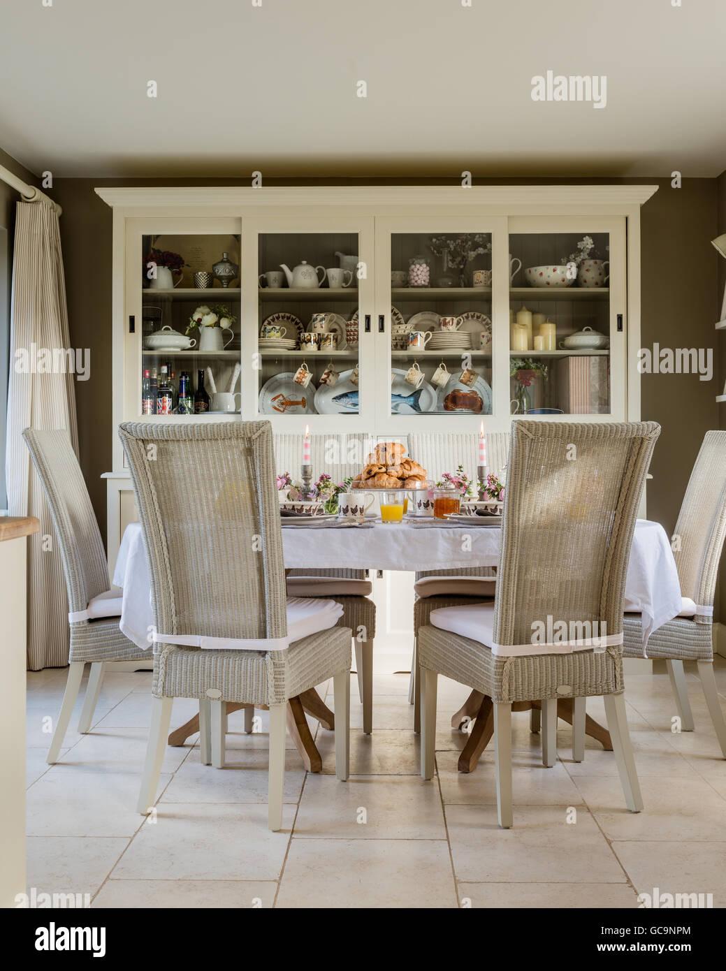 Fulham Lloyd Loom Stühle Tisch mit Croissant gelegt. Eine große weiße Kommode steht im Hintergrund Stockbild