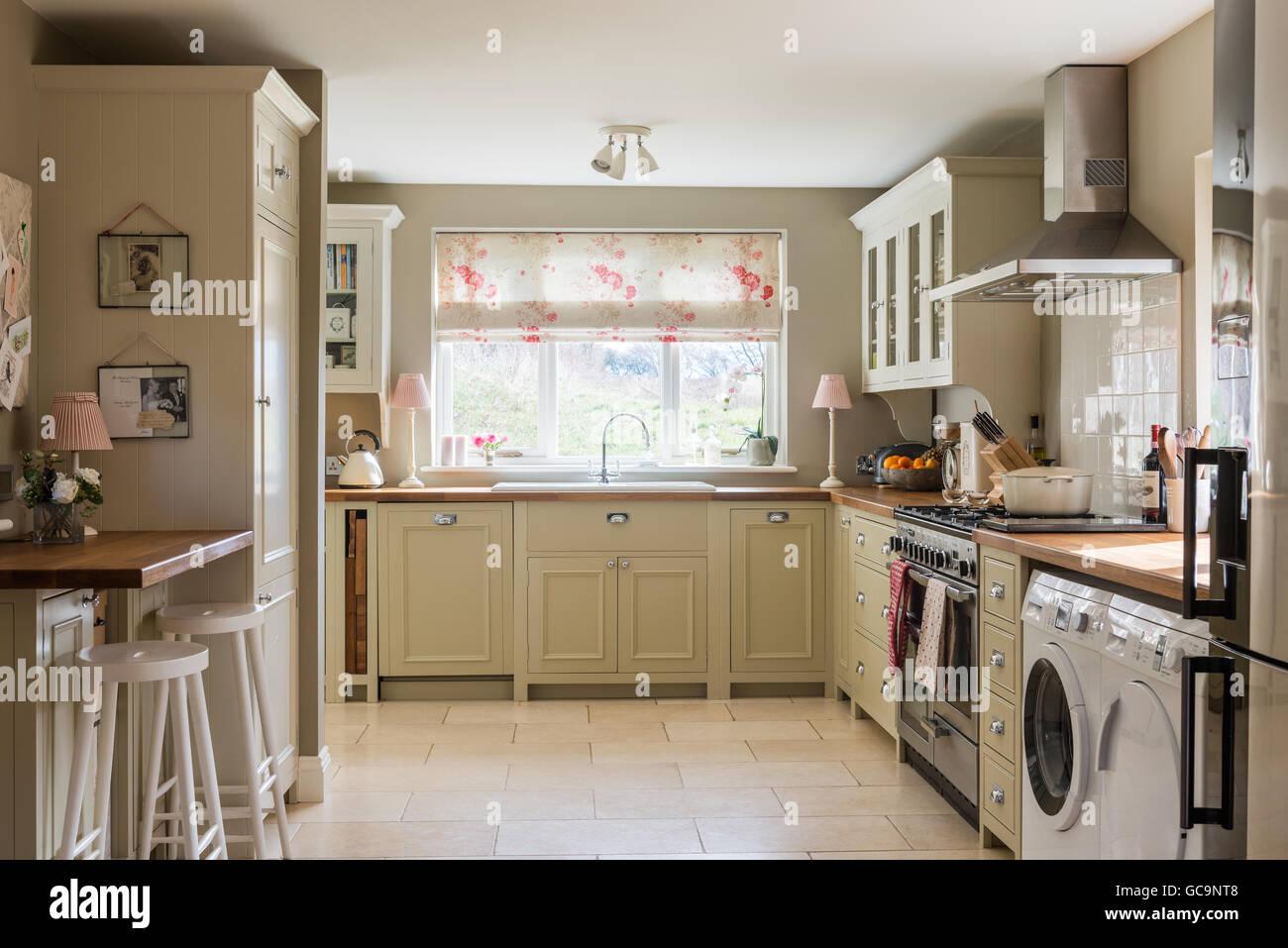 Landhausküche mit Einheiten von Neptun und getrommelt Kalkstein Bodenfliesen. Die Faltrollos besteht in Kate Stockbild