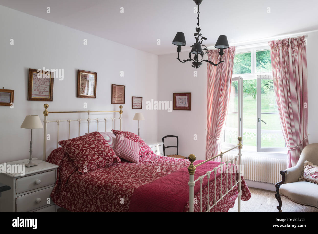 Viktorianische Messing-Bett mit roten und weißen Decke. Die Vorhänge ...