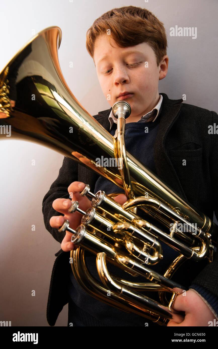 11 - jähriger Junge mit einem Bariton-Horn Stockbild