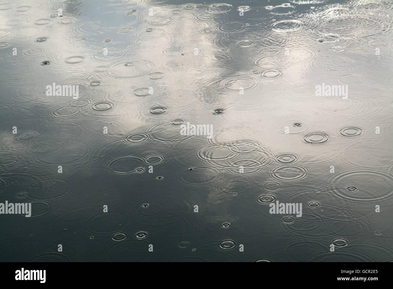 Tröpfchen Regen schlagen ein ruhiges Meer Stockbild
