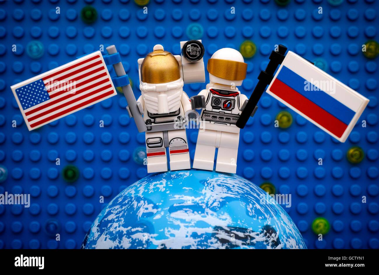 Zwei Lego-Spaceman-Minifiguren mit amerikanischen und russischen Fahnen bleiben auf Planeten gegen Lego blaue Grundplatte Stockbild