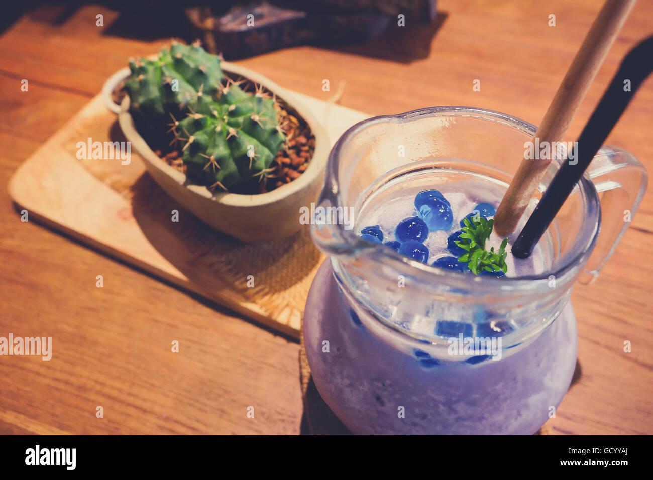 Heidelbeer-Smoothie mit Minze im Einmachglas Becher mit Strohhalm und Kaktus. Über Ansicht auf Holz. Stockfoto