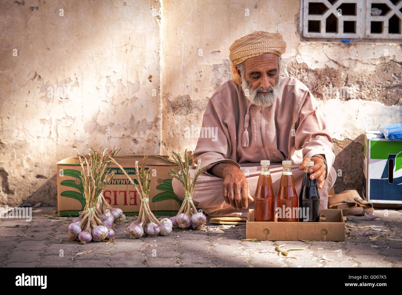 NIZWA, OMAN - 24 APRIL 2015:Omani Greis, Verkauf von Honig und Knoblauch auf dem traditionellen Markt oder Souk Stockbild