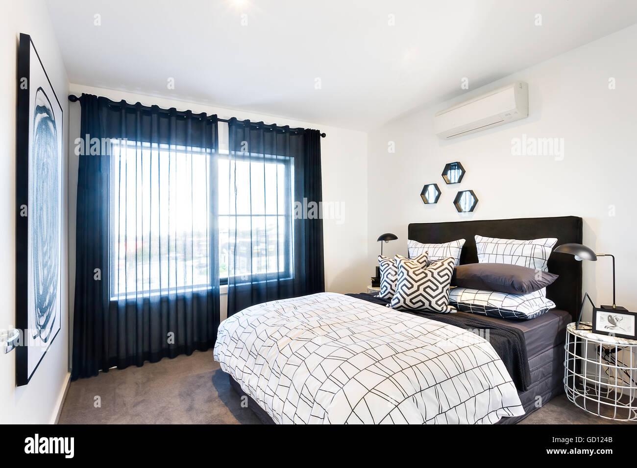 Luxus Schlafzimmer Mit Sonnenlicht Durch Den Schwarzen Vorhang Neben Das  Bett Und Die Kissen In Der Nähe Der Lampen Beleuchtet