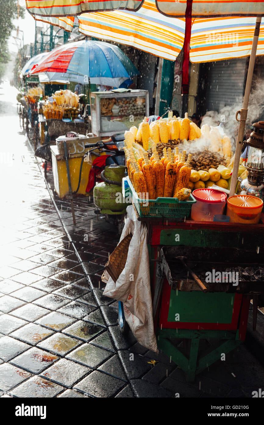 Straße Garküche mit gegrilltem Mais unter dem Regen, Ubud, Bali, Indonesien Stockbild