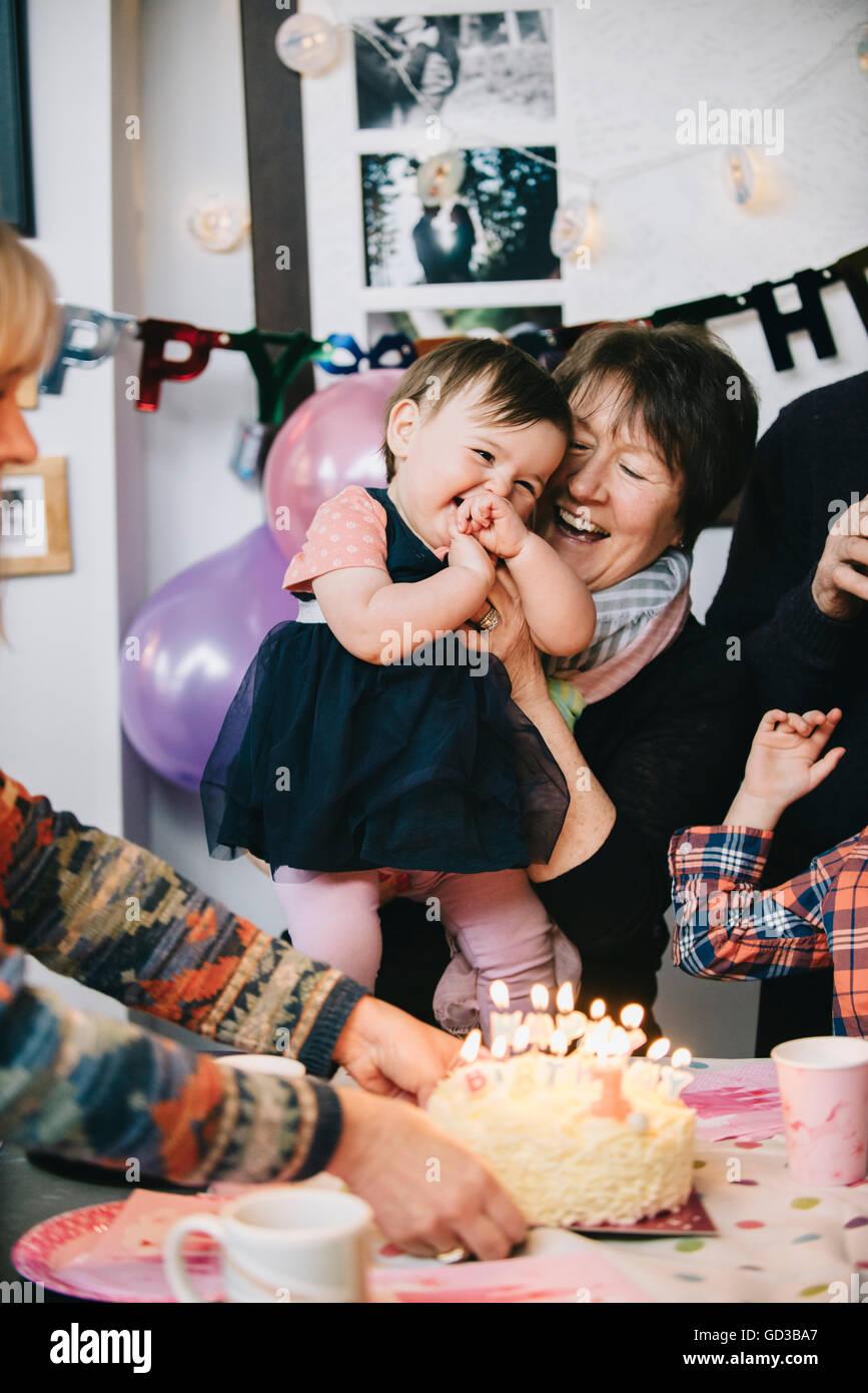 Eine Familie versammelt, um ein einjähriges Mädchen-Geburtstags-Party zu feiern. Ein Kuchen mit vielen Stockbild