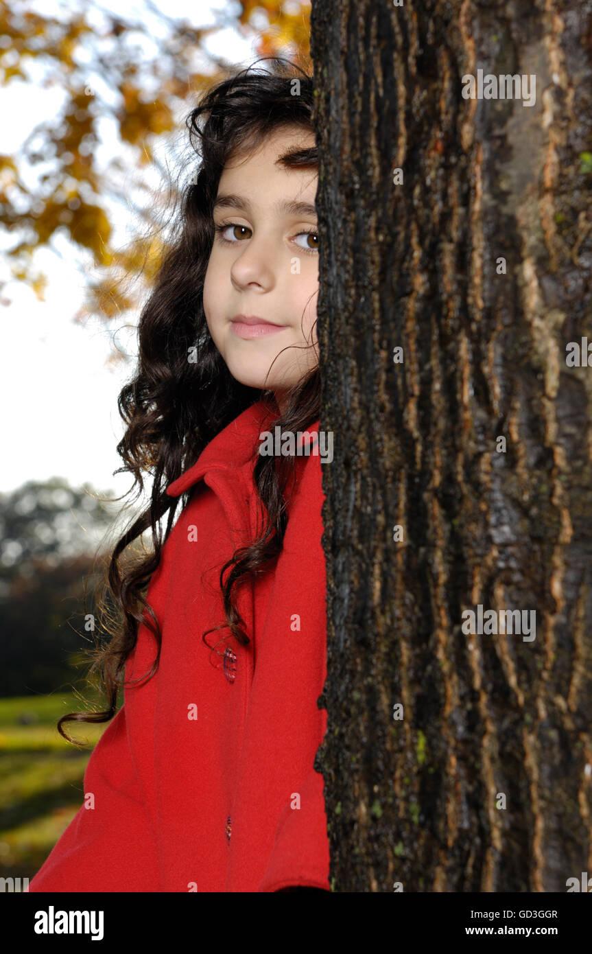 Fünf Jahre altes Mädchen im roten Mantel stehen in der Nähe von einem Baum in einem park Stockfoto