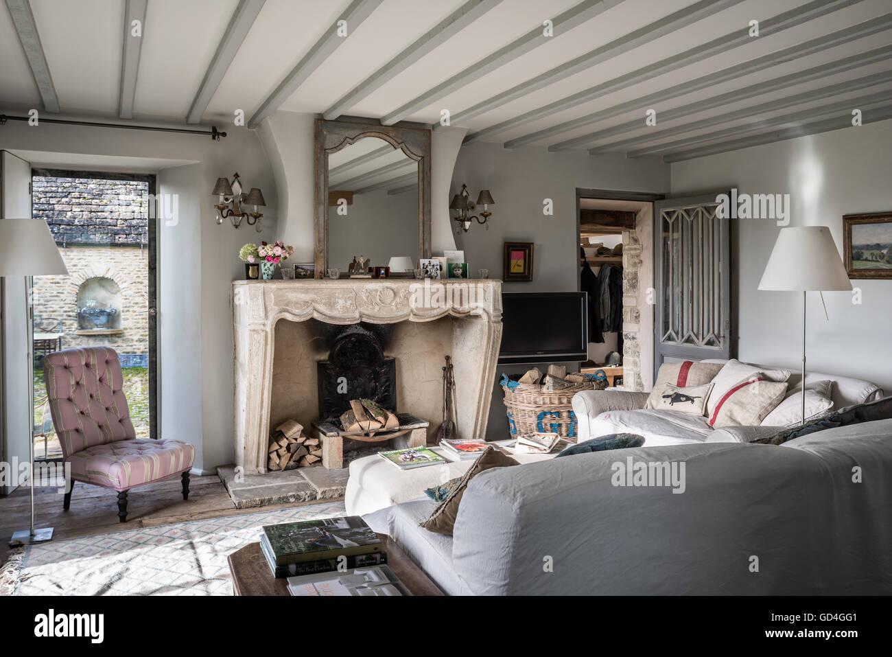 Französischen Kamin mit Leinen Slip bedeckt Polster und zugeknöpft Stuhl Stockbild