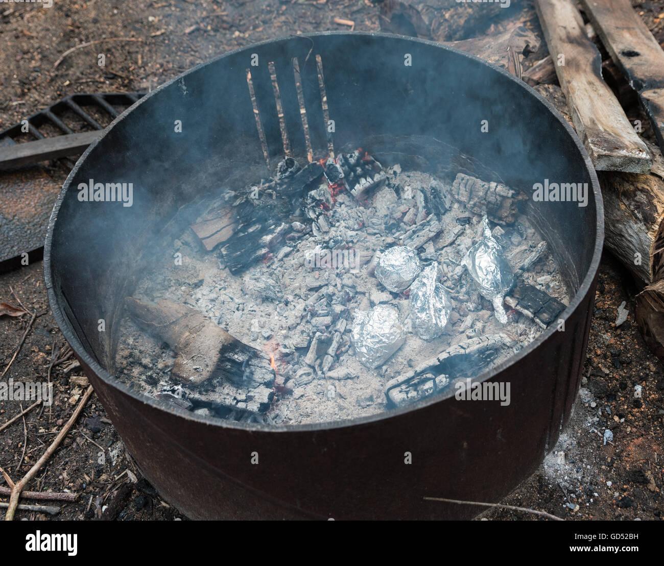 Kartoffeln in Folie Kochen auf heißen Kohlen im Feuer gewickelt Stockfoto
