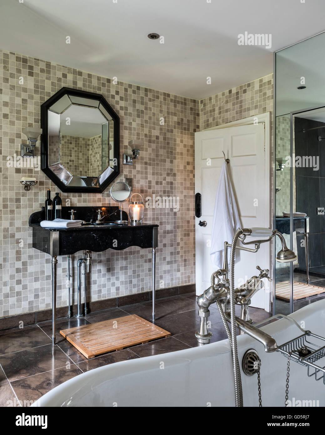 Sechseckige Spiegel über Wäsche stehen in gefliesten Badezimmer des ...