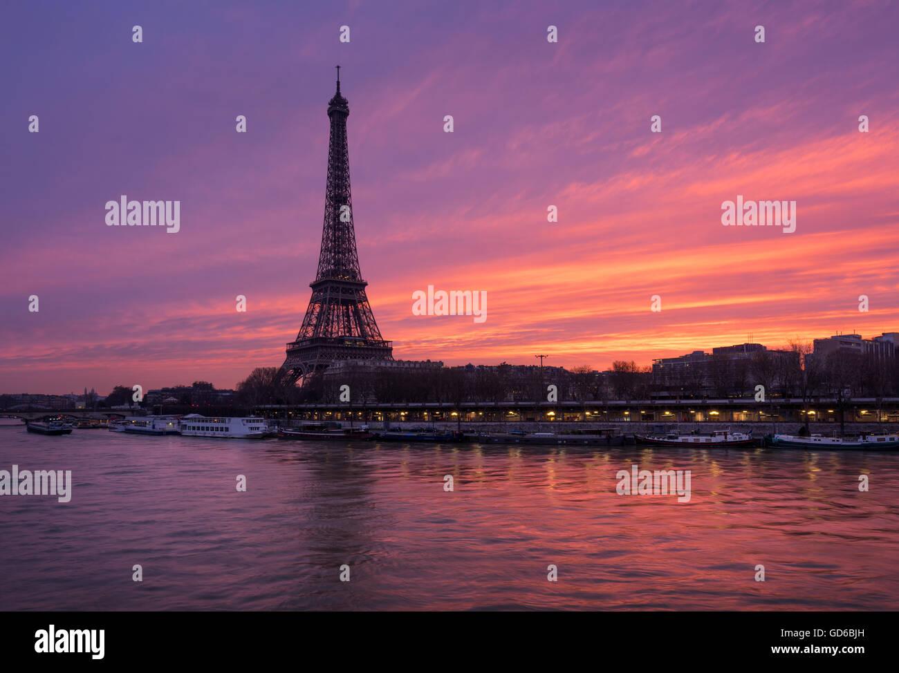 Feurige Sonnenaufgang auf dem Eiffelturm und Seineufer mit Port de Suffren, Paris (7. und 15. Arrondissement) Stockbild