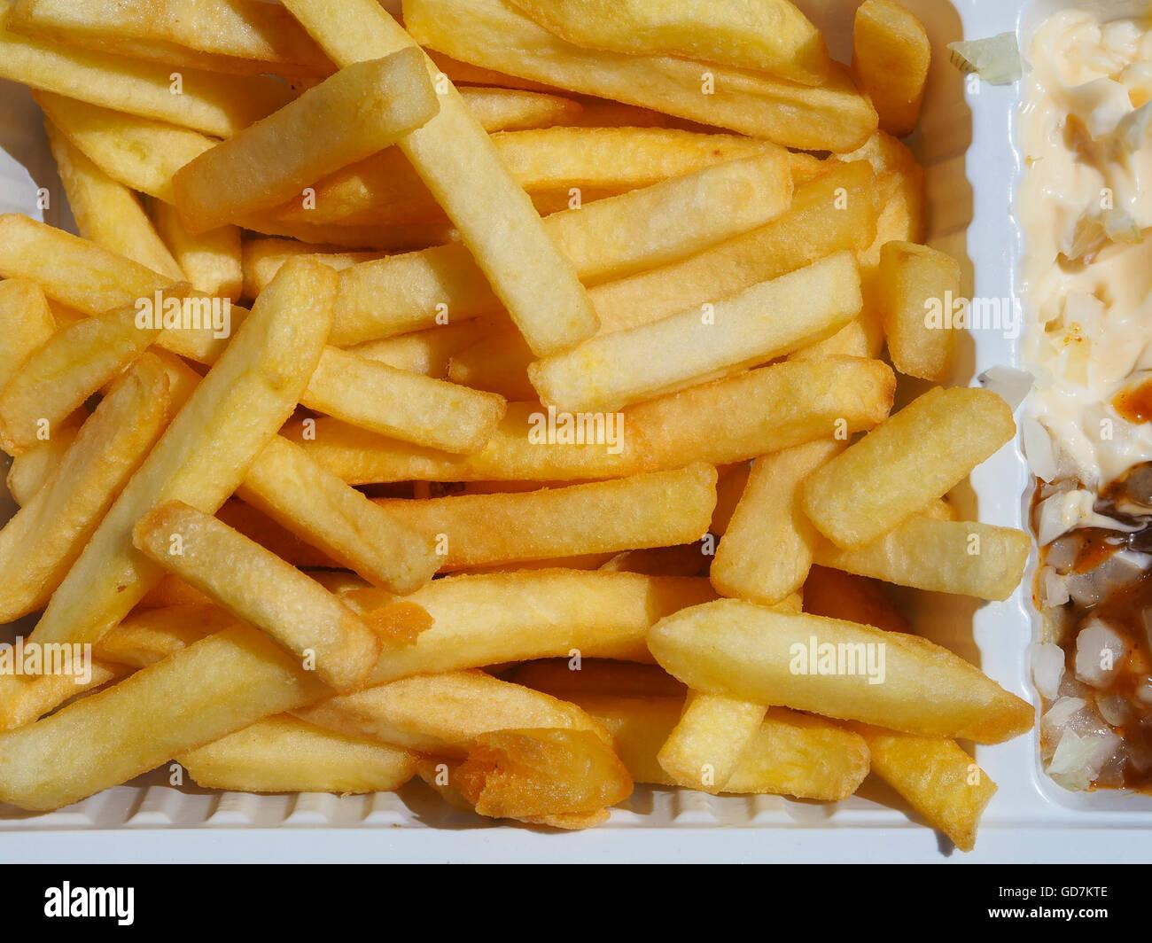 Nahaufnahme der goldene Pommes Kartoffelchips in einer weißen Plastikschale mit mayonnaise Stockbild