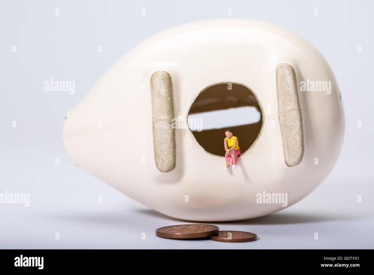 Konzept-Bild der eine einsame Gestalt mit einer leeren Sparschwein zu geringen Einsparungen und niedrige Zinsen Stockbild