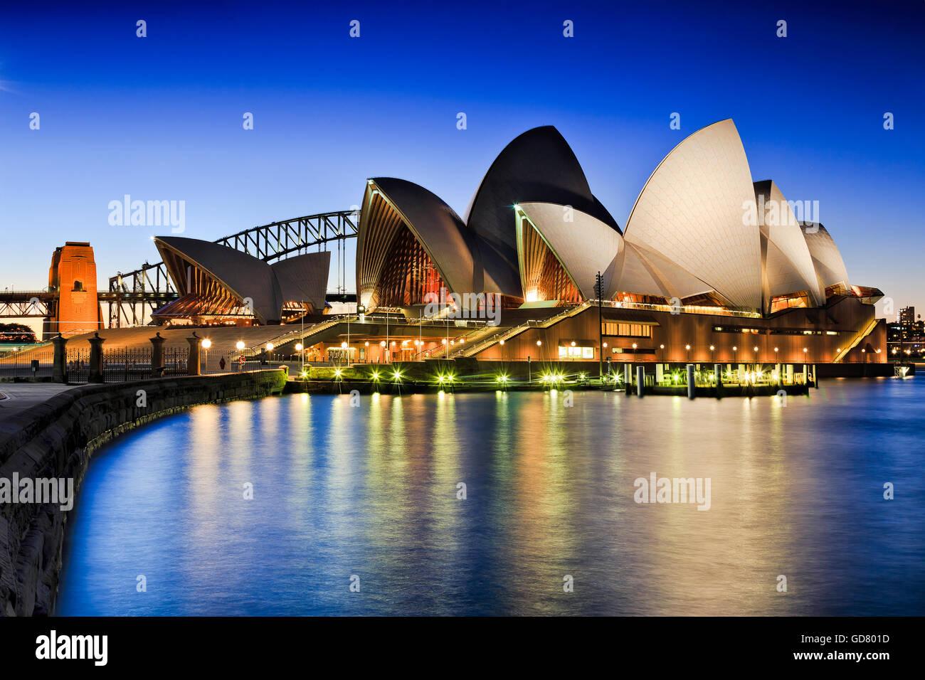 SYDNEY, Australien, 1. Juli 2016 - Sydney Opera House und Harbour Bridge bei Sonnenuntergang reflektierende Beleuchtung Stockbild