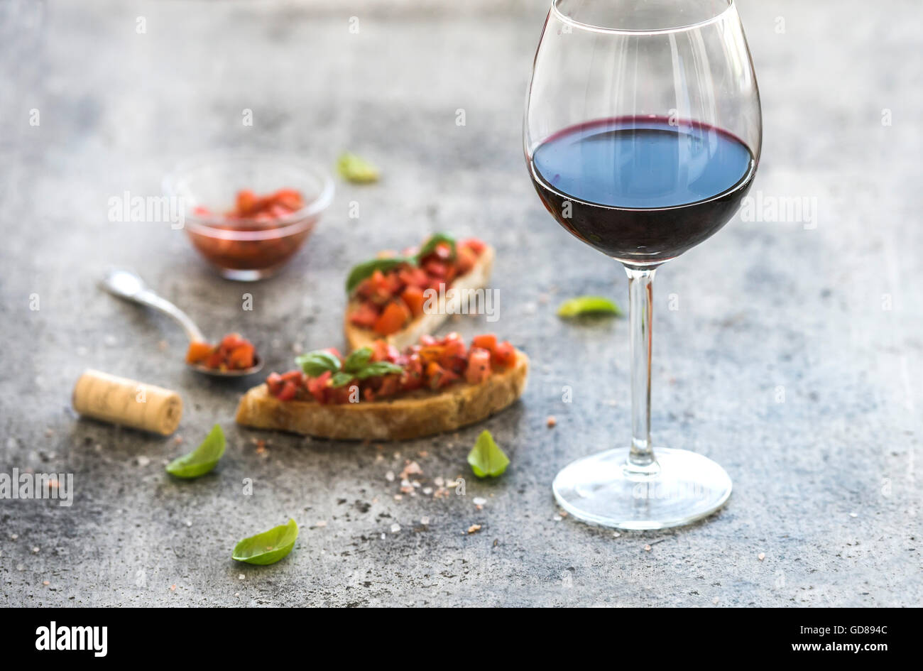 Glas Rotwein und Kanapees mit Tomaten und Basilikum, Tiefenschärfe, horizontale Komposition Stockbild